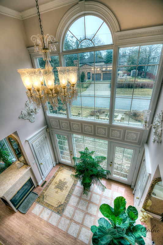 Looking down from the second floor to the home's east-facing doors. Natural wood and marble are also in keeping with the principles used in many ancient temples and buildings. Glenn Ogilvie