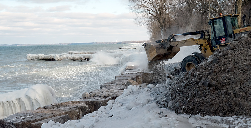A backhoe from Van Bree Drainage and Bulldozing backfills a repaired section of the Lake Huron Shoreline just east of the Cull Drain Bridge.