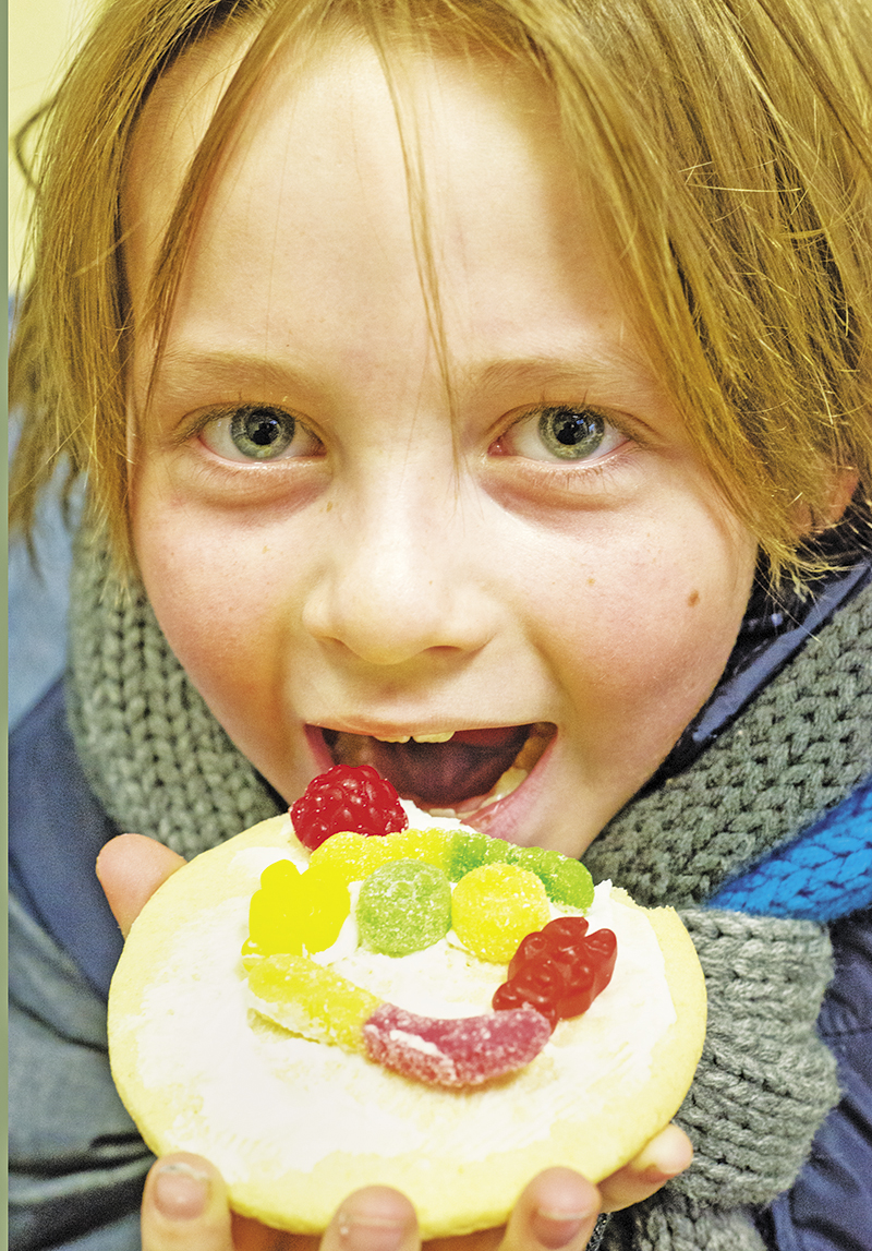 Dylan Branton, 8, the son of Melanie and Kevin, of Corunna,  samples a tastefully decorated cookie he made at the Secret Santa Shop on Nov. 21 Glenn Ogilvie