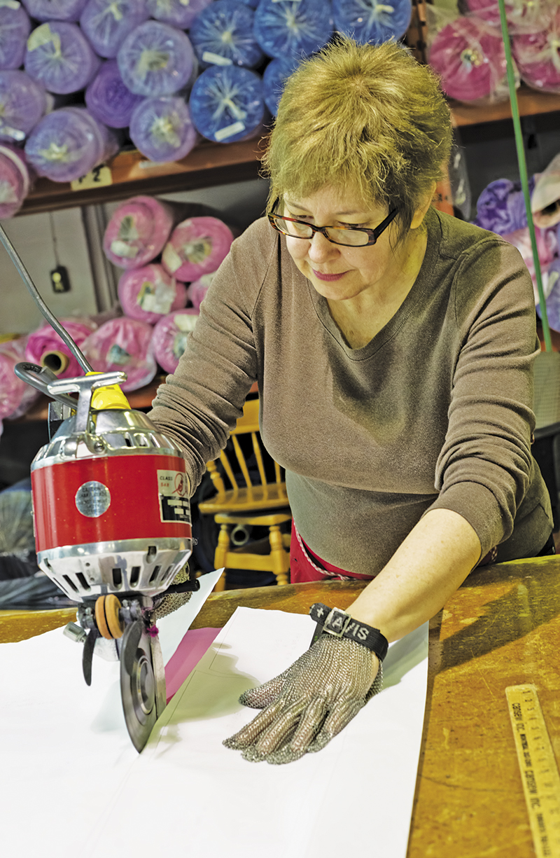 Karen Folk cuts patterns for 20 layers of material used to make girls costume dresses at the Point Edward manufacturing Centre. Glenn Ogilvie